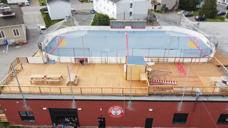 Des gens d'affaires construisent une surface de dek hockey sur un toit