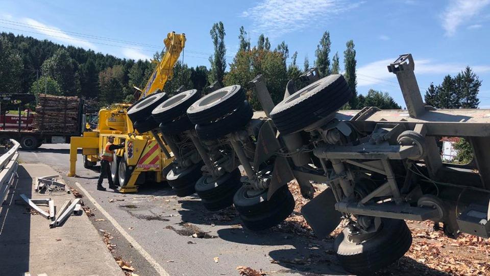 Un camion lourd renverse sur le côté avec son chargement de bois